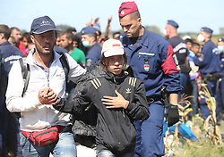 © London News Pictures. © London News Pictures. Migrants  break through a police corden to board a bus close to the Hungarian and Serbian border town of Roszke, Hungary, September 7 2015. The UN's humanitarian agencies are on the verge of bankruptcy and unable to meet the basic needs of millions of people because of the size of the refugee crisis in the Middle East, Africa and Europe, senior figures within the UN have told the media.   Picture by Paul Hackett /LNP