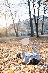 Mature woman reading book lying down on fallen leaves in the park, Bavaria, Germany