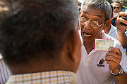 """01 FEBRUARY 2014 - BANGKOK, THAILAND: A Thai voter confronts an election worker with his ID card. The man was told he couldn't vote because protestors had blocked the polls. Thais went to the polls in a """"snap election"""" Sunday called in December after Prime Minister Yingluck Shinawatra dissolved the parliament in the face of large anti-government protests in Bangkok. The anti-government opposition, led by the People's Democratic Reform Committee (PDRC), called for a boycott of the election and threatened to disrupt voting. Many polling places in Bangkok were closed by protestors who blocked access to the polls or distribution of ballots. The result of the election are likely to be contested in the Thai Constitutional Court and may be invalidated because there won't be quorum in the Thai parliament.    PHOTO BY JACK KURTZ"""