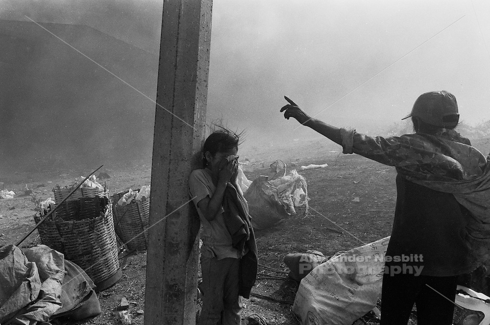 Municipal dump, Oaxaca, Mexico 1998 - A girl cries from fear while her older sister yells directions. Months of the family's work is lost as the scavenged materials they collected from the dump go up in flames during a spontaneous dump fire...In the municipal dump a self governed group of 80 individuals and families eke out a living.  Los Pepenadors (the Pickers) work in a landscape of garbage and flames, blanketed by toxic smoke, along side bulldozers and garbage trucks.  They do the impossible job of recycling what the rest of their society can't be bothered to deal with. ..