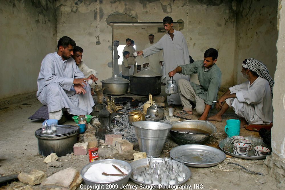 Young men and boys from the village prepare coffee and tea in a motheff, a traditional long house, during the Al-Kasid family's Istikbal, or homecoming, in their home village Suq ash Shuyukh about 20 miles southeast of Nasiriyah, Iraq, July 30, 2003. ..The boys work throughout the 3 day celebration fetching water, serving food, cleaning, etc., which teaches them respect for their elders. In return, they are fed better than normal and get to be a part of the action as this was a huge event in the village...The Al-Kasid family fled Iraq after the Gulf War and their part in the uprising against Saddam Hussein in 1991, spent 3 years in Rafa, Saudi Arabia and finally settled in Dearborn, MI. The family hasn't been home to Iraq in 13 years. After their participation in the 1991 uprising, Saddam Hussein's forces burned the Al-Kasid family Motheff, along with their cars, to the ground.