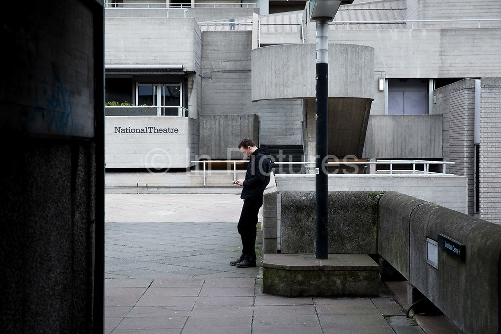 A man checks his mobile phone outside The National Theatre building on 10th January 2017 in London, United Kingdom. The National Theatre along the Southbank, designed by Denys Lasdun, is one of Londons best-known and most divisive Brutalist buildings. From the series Our Small World, an observation of our mobile phone obsessions