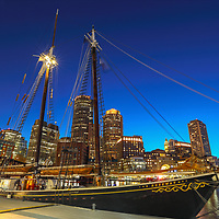 Sail Boston tall ship Roseway moored at Fan Pier in the Boston Harbor with waterfront skyline photography from New England photographer Juergen Roth. The image shows the historic sailboat in front of the Boston Financial Waterfront District landmarks such as the Custom House of Boston, One International Place, Boston Harbor Hotel photographed on a beautiful summer sunset evening. <br />