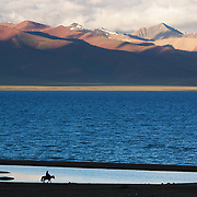 A lone rider on the shores of a lake in Tibet.