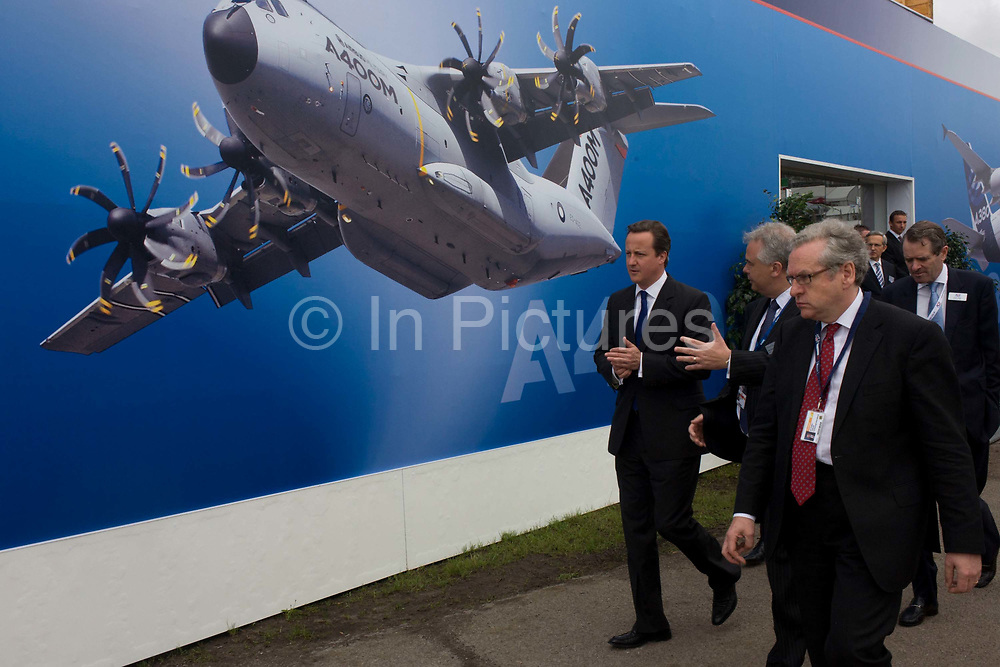 British Prime Minister David Cameron walks past one of the Airbus exhibition stands at the Farnborough Air Show, England. Helping to launch this expo held for the international aviation and aerospace industries, Cameron toured stands to help promote trade and investment for this 48th airshow (FIA) and hailed the phenomenal success of the UK aerospace industry and its critical importance to growth and jobs.Farnborough is attended by an international business audience including 83 trade and military delegations from over 43 countries. The Airbus A400M Atlas, is a multi-national four-engine turboprop military transport aircraft. It was designed by Airbus Military as a tactical airlifter with strategic capabilities. The aircraft's maiden flight, originally planned for 2008, took place on 11 December 2009 in Seville, Spain.