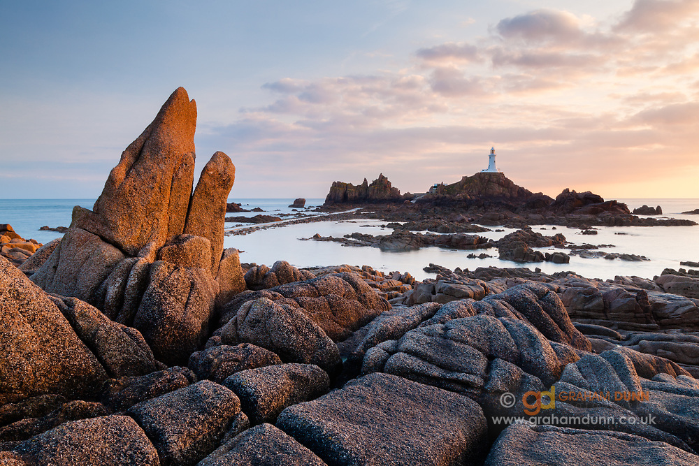Evening sun lights the dramatic foreground rocks with Corbière Lighthouse in the distance. La Corbière, Jersey, Channel Islands, UK.