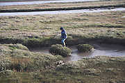 Boy walking over salt marsh, Shingle Street Orford Ness spit, Suffolk, England