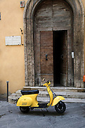 Yellow Vespa scooter. Photographed in Montepulciano, Tuscany, Italy