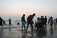Cox's Bazar, Bangladesh - October 27, 2017: A crowd of people, including a man in a wheelchair, enjoy the beach at sunset in Cox's Bazar.