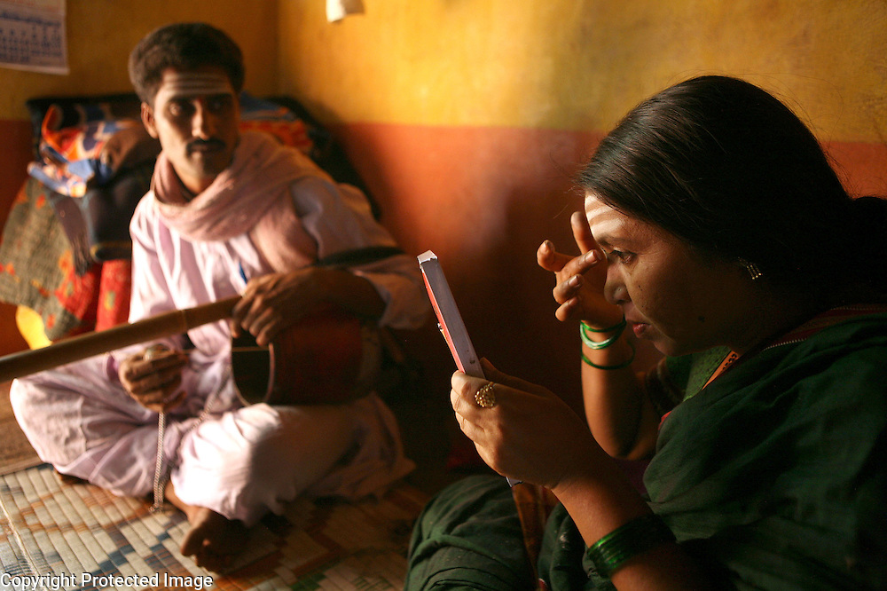 """Radhabai Madar Mudalagi (right) was dedicated as a Devadasi by her parents at a very young age.  Now in her early forties, she lives in the small village of Yellamanawadi and uses the Devadasi musical tradition called """"Chowdike Pada"""" to educate her audiences about social issues, particularly, the Devadasi system. Accompanied by her husband, Mrutunjaya Mudalagi, (left) who plays an instrument called the shruti that resembles a guitar, Radhabai was even recorded for a television program which was broadcasted to small villages all over Karnataka and other states as part of a social education program.  Because of her activism coupled with the fact that she defied the Devadasi system and married a man, she has been rejected by her community. ."""