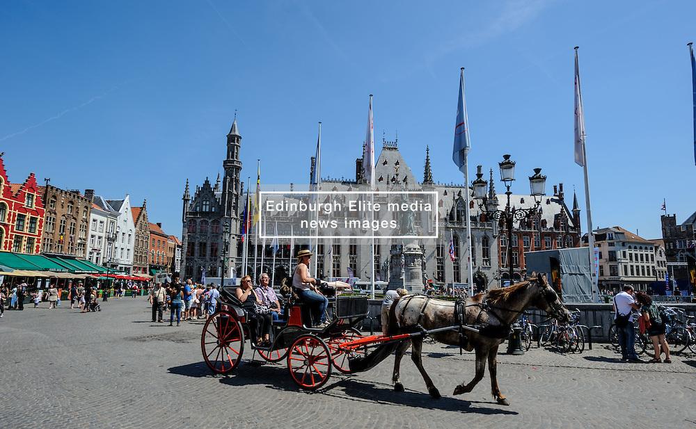 Horse drawn carriage carrying tourists in Grote Markt, Bruges, Belgium<br /> <br /> (c) Andrew Wilson   Edinburgh Elite media