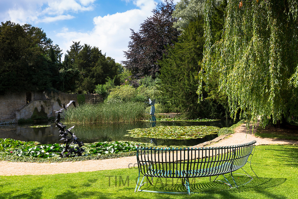 Sculptures of flying swans and 29 terns in bronze by Lloyd Le Blanc at the lake at Le Manor Aux Quat' Saisons in Oxfordshire, UK