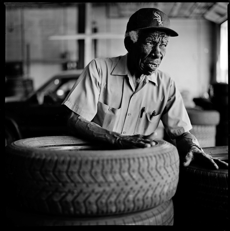 """L.C. Caviness, 78, presides over used tire sales at National Brake & Alignment on a stretch of Truman Road where he has worked for 60 years. """"You gotta understand the people....I have a story for everybody....I can make 'em laugh, I can make 'em cry."""""""