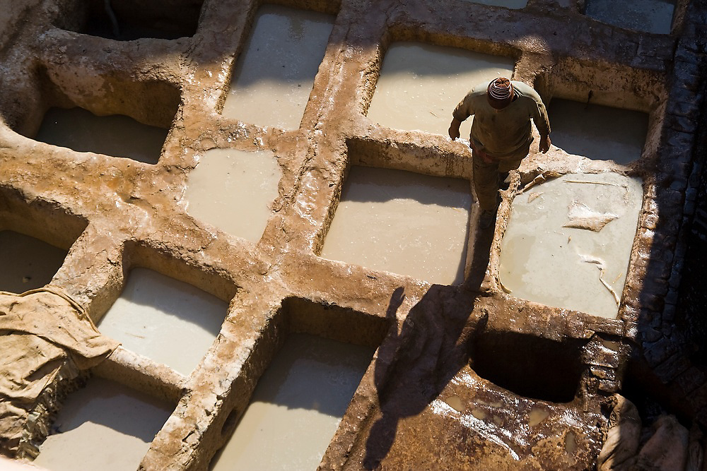 A man walks among the lime pits at the Berber leather tannery in Fes El-Bali, Morocco.