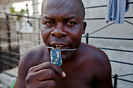 Voodoo priest George Raul's wears a dog tag and a medallion with President Obama on it . Raul's practices voodoo in the  The National Cemetery in Haiti.<br /> Haitian Voodoo is a syncretic religion that originates in  Haiti based upon a merging of the beliefs and practices of West African peoples with Arawakian religious beliefs, and Roman Catholic Christianity.
