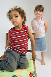 Portrait of young brother and sister; looking mischievous,