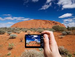 Tourist photographing Uluru in Australia with a digital  camera