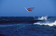 A wind surfer leaps a wave. Hawaii.
