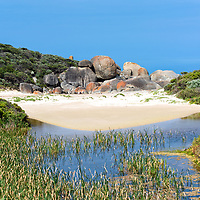 Massive boulders flank the golden beach sands of Whisky Bay, Wilsons Promontory National Park, Victoria, Australia.