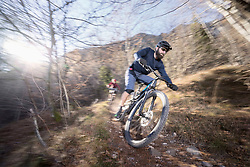 Mountain bikers riding downhill in alpine landscape, Trentino, Italy