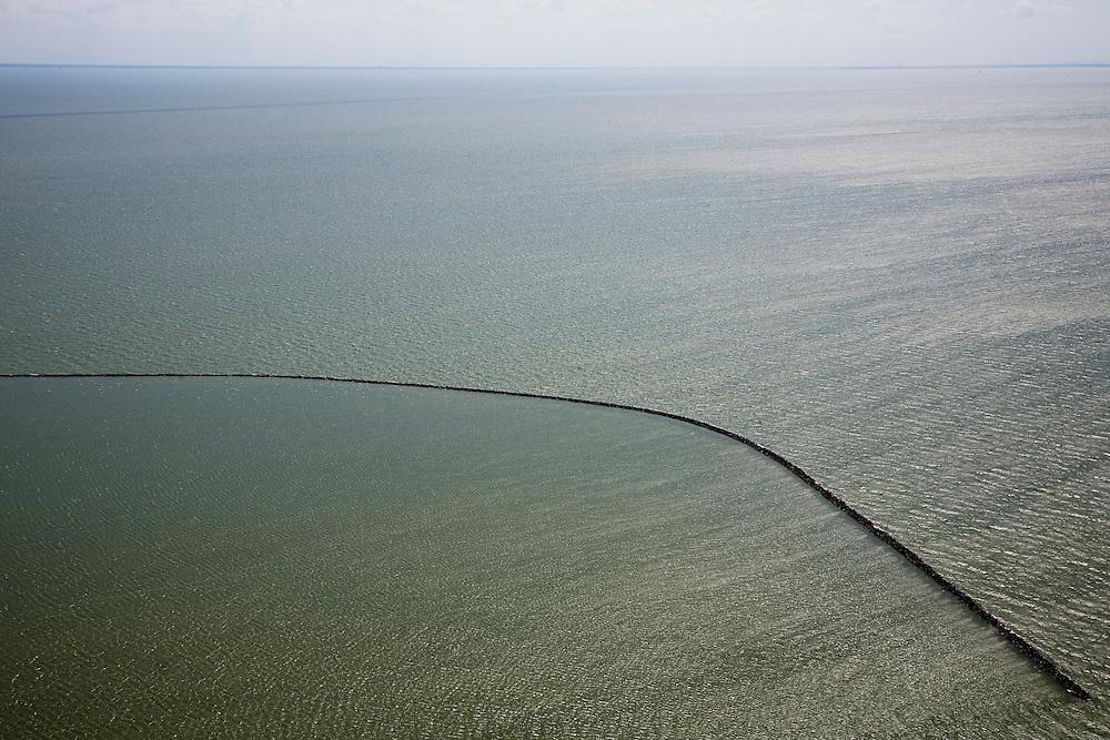 Nederland, Noord-Holland, IJsselmeer, 14-07-2008; Markermeer, strekdam van basaltblokken aangelegd ter bescherming van de Houtribdijk, in de achtergrond de contouren van kust van Noord-Holland; de Houtribdijk verbindt Enkhuizen en Lelystad en deelt het IJsselmeer in IJsselmeer en Markermeer; de dijk is oorpronkelijk aangelegd om het Markeermeer in te polderen (Markerwaard), deze inpoldering maakte reeds deeluit van de Zuiderzeewerken; andere namen voor de dijk zijn: Markerwaarddijk, Lelydijk en Dijk Enkhuizen-Lelystad N302; toekomst, algen, licht, leeg, leegte, Lely,. .luchtfoto (toeslag); aerial photo (additional fee required); .foto Siebe Swart / photo Siebe Swart.;