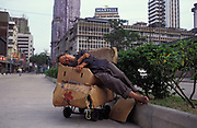 A market trader takes a mid-day sleep in the middle of the road, on 10th August 1994, in Macau, China. Macau is now administered by China as a Special Economic Region SER, home to a population of mainland 95% Chinese, primarily Cantonese, Fujianese as well as some Hakka, Shanghainese and overseas Chinese immigrants from Southeast Asia and elsewhere. The remainder are of Portuguese or mixed Chinese-Portuguese ancestry, the so-called Macanese, as well as several thousand Filipino and Thai nationals. The official languages are Portuguese and Chinese.