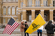 "02 JANUARY 2021 - DES MOINES, IOWA: People carry flags in front of the Iowa State Capitol. About 30 people marched around the Iowa State Capitol Saturday afternoon to protest the outcome of the November 3 general election in the United States. They are a part of the ""Stop the Steal"" movement which maintains that the election was stolen from Donald Trump by massive voter fraud. There is no evidence supporting their conspiracy theory. This is the 9th week Donald Trump supporters have marched around the Capitol. They've been there every week since the Nov. 3 election. More than 1,000 people showed up the first week, but the crowd has gotten smaller every week.   PHOTO BY JACK KURTZ"