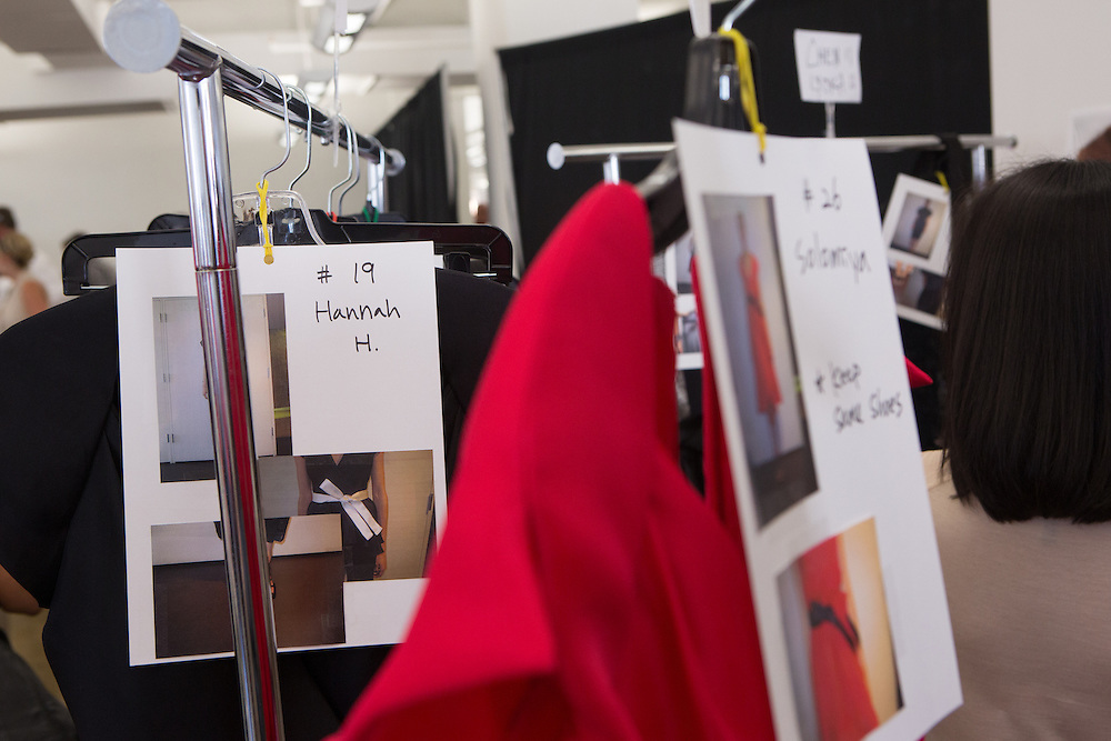 Dressing cards and dresses await models backstage at the Carmen Marc Valvo Spring 2013 Fashion Week show in New York.
