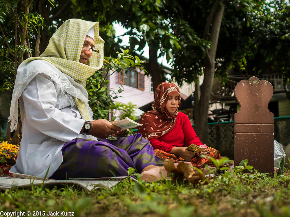 17 JULY 2015 - BANGKOK, THAILAND:     A man and his wife pray at a grave in the cemetery of Bang Luang Mosque after Eid services at the mosque in Bangkok. Eid al-Fitr is also called Feast of Breaking the Fast, the Sugar Feast, Bayram (Bajram), the Sweet Festival or Hari Raya Puasa and the Lesser Eid. It is an important Muslim religious holiday that marks the end of Ramadan, the Islamic holy month of fasting. Muslims are not allowed to fast on Eid. The holiday celebrates the conclusion of the 29 or 30 days of dawn-to-sunset fasting Muslims do during the month of Ramadan. Islam is the second largest religion in Thailand. Government sources say about 5% of Thais are Muslim, many in the Muslim community say the number is closer to 10%.          PHOTO BY JACK KURTZ