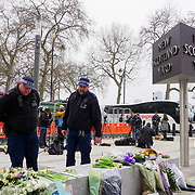 Two police looking at the Flower tributes at New Scotland Yard for the victims of the Tuesday's 21th March 2017 attack on Westminster Bridge and in the grounds of Parliament, in London, Friday, March 24, 2017. by See Li