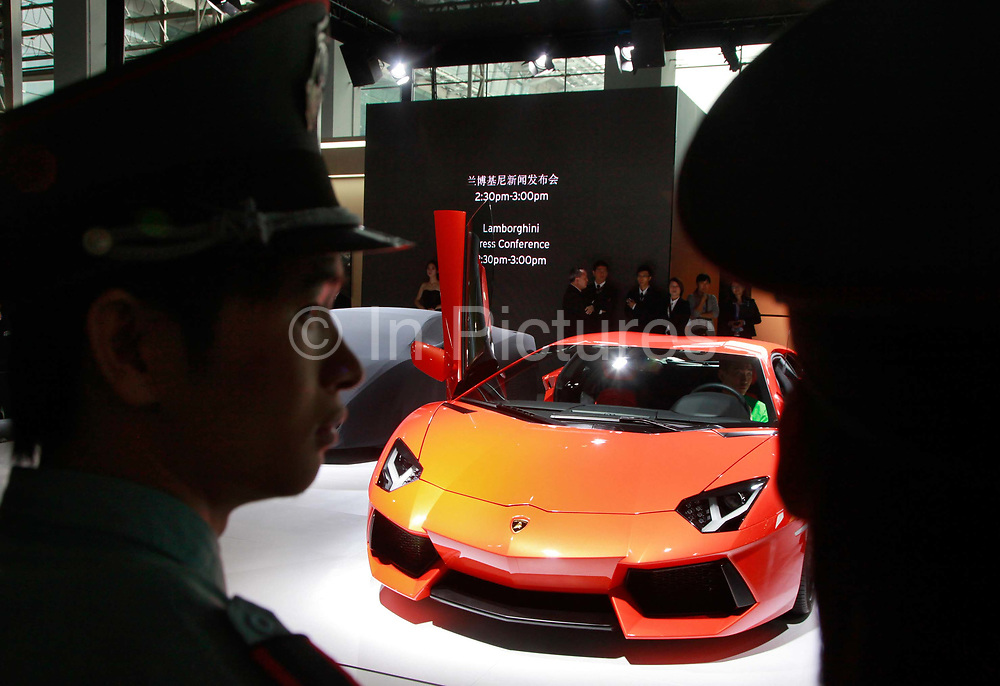 Security guards look at Lamborghini SpA sports vehicles during the the China ( Guangzhou) International Automobile Exhibition in Guangzhou, Guangdong Province, China, on Monday, Nov. 21, 2011. Despite signs of slowing, China remains the largest and fastest growing market for international car makers, especially in the luxury sector.