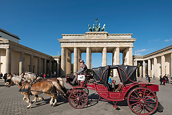 Horsedrawn carriage passes in front of Brandenburg Gate in Berlin Germany
