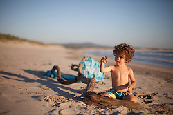 Small boy playing with driftwood on the beach, Viana do Castelo, Norte Region, Portugal