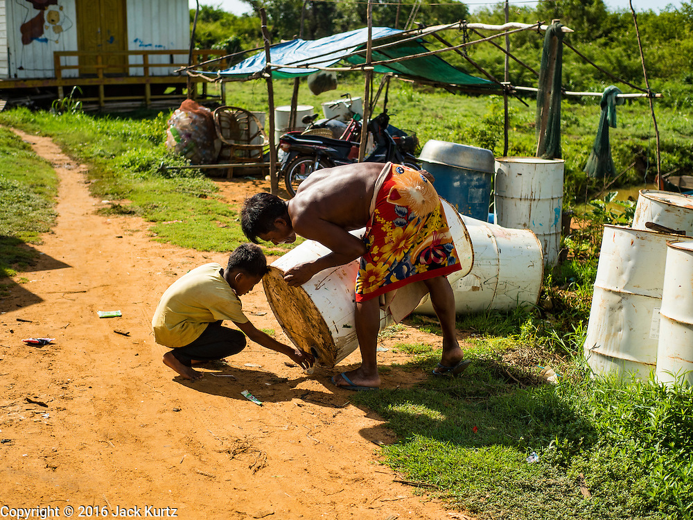 31 MAY 2016 - SIEM REAP, CAMBODIA: A man and boy get kerosene from a nearly empty drum in their village, where the Tara is beached. The kerosene drums will be put under the houses in the village and used as to float the houses if the area floods in the coming rainy season. The Tara is a river freighter and passenger boat assembled in Vietnam, then a French colony, in 1927. Most recently it's used to take tourists on dinner cruises on the Tonle Sap Lake. Because of the drought in Cambodia, the Tara is beached and unable to navigate the nearly empty canals that lead to the Tonle Sap Lake. The boat's owners are repairing and refurbishing it while it's beached and hope that the coming rainy season will flood the canal enough to let the Tara get back to the lake.    PHOTO BY JACK KURTZ
