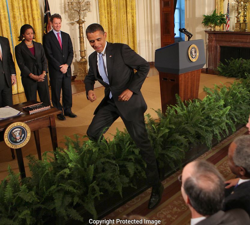 After signing the Iran Sanctions Act President Barack Obama step over flowers rimming the stage to shake hands with the first row of the audience.  Photograph by Dennis Brack