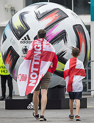 © Licensed to London News Pictures. 08/07/2021. London, UK. England fans walk past a giant replica football outside  Wembley Stadium the morning after England beat Denmark in the Euro 2020 semi final, to reach their first final since 1966. Photo credit: Ben Cawthra/LNP