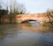Red brick bridge spanning the swollen River Deben after heavy rain, Ufford, Suffolk, England