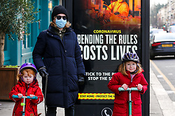 © Licensed to London News Pictures. 18/01/2021. London, UK. Elizabeth wearing a protective face covering, with Wilson aged 5 year old (R) and Ellis aged 2 years old (R) walk past the government's 'Bending The Rules Costs Lives' publicity campaign poster in north London, after the mutated variant of the SARS-Cov-2 virus continues to spread around the country. People in England aged 70 and over have started to receive offers of a coronavirus vaccine from today. The government could lift the lockdown in March, after people aged 70 and above have been vaccinated. Every adult in the UK will be offered a first dose of a coronavirus vaccine by September. <br /> <br /> ***Permission Granted***<br /> <br /> Photo credit: Dinendra Haria/LNP
