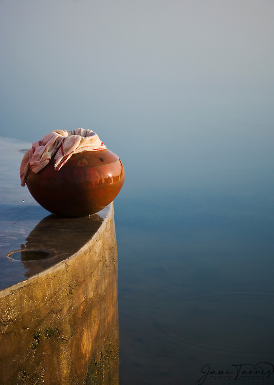 Still life of an indian ceramic water pot overlooking a river after being filled with water by a village tribal girl, sunrise, Phalodi, Rajasthan, India