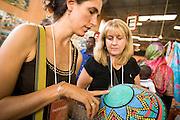 Professional buyers looks at a basket at the 22nd Salon International de l'Artisanat de Ouagadougou (SIAO) in Ouagadougou, Burkina Faso on Sunday November 2, 2008.