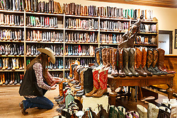 Lady shopping for boots at M.L Leddy's Boots, Fort Worth Stockyards National Historic District, Fort Worth, Texas, USA.