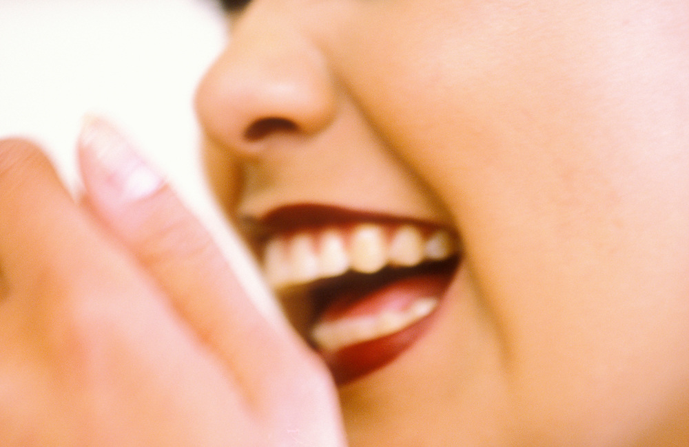 Closeup of a womans mouth while laughing.  Partially obscurred by hand.