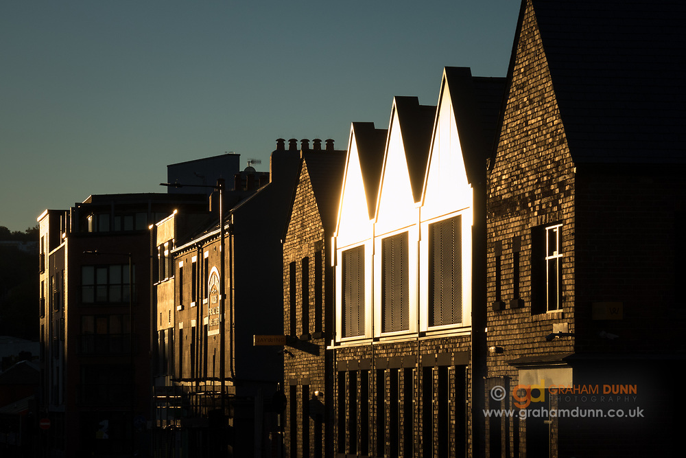 Low morning sunlight shines brilliantly off this triplet of gable ends on Matilda Street in Sheffield. An urban landscape scene in South Yorkshire, England, UK.