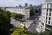Seen from the elevation from the Marble Arch Mound, a yellow London bus drives across the junction of Bayswater Road and the southern end of Edgeware Road, on 11th August 2021, in London, England.