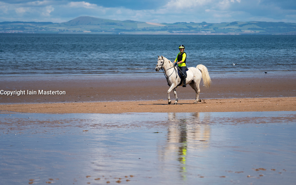 Gullane, Scotland, UK. 9 July, 2020. Signs and one-way system on beach paths have been introduced at beaches in East Lothian. To maintain social distancing some paths are one-way only. Pictured; Woman riding a horse on Gullane Beach.  Iain Masterton/Alamy Live News