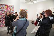 POSING IN MASKS WITH ARTWORK, Frieze. Regent's Park. London. 17 October 2013