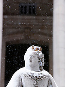 A statue of Queen Victoria outside of St Pauls Cathedral covered in snow in London, UK