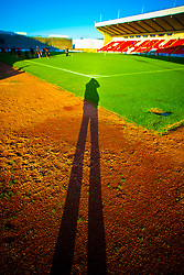 Shadow of the photographer at Broadwood Stadium, also referred to as simply Broadwood, is a football stadium and multi-use community sports complex situated in Cumbernauld, North Lanarkshire, Scotland. It is the home venue of Scottish Third Division side, Clyde F.C.