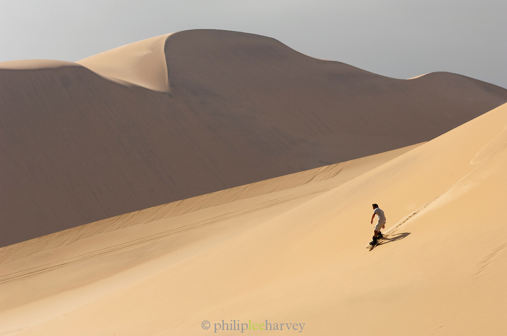 Man sandboarding down a large dune in the Namib Desert near Swakopmund, Namibia