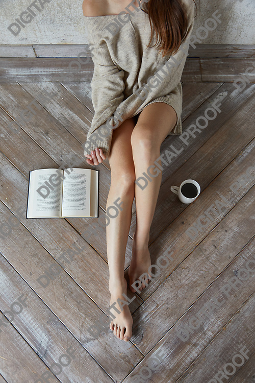 Concept of a Lazy day with a  young woman wearing a sweater sitting on wooden floor with detail of brown hair and shoulder skin, an aopen book and a mug of coffee, top and above view
